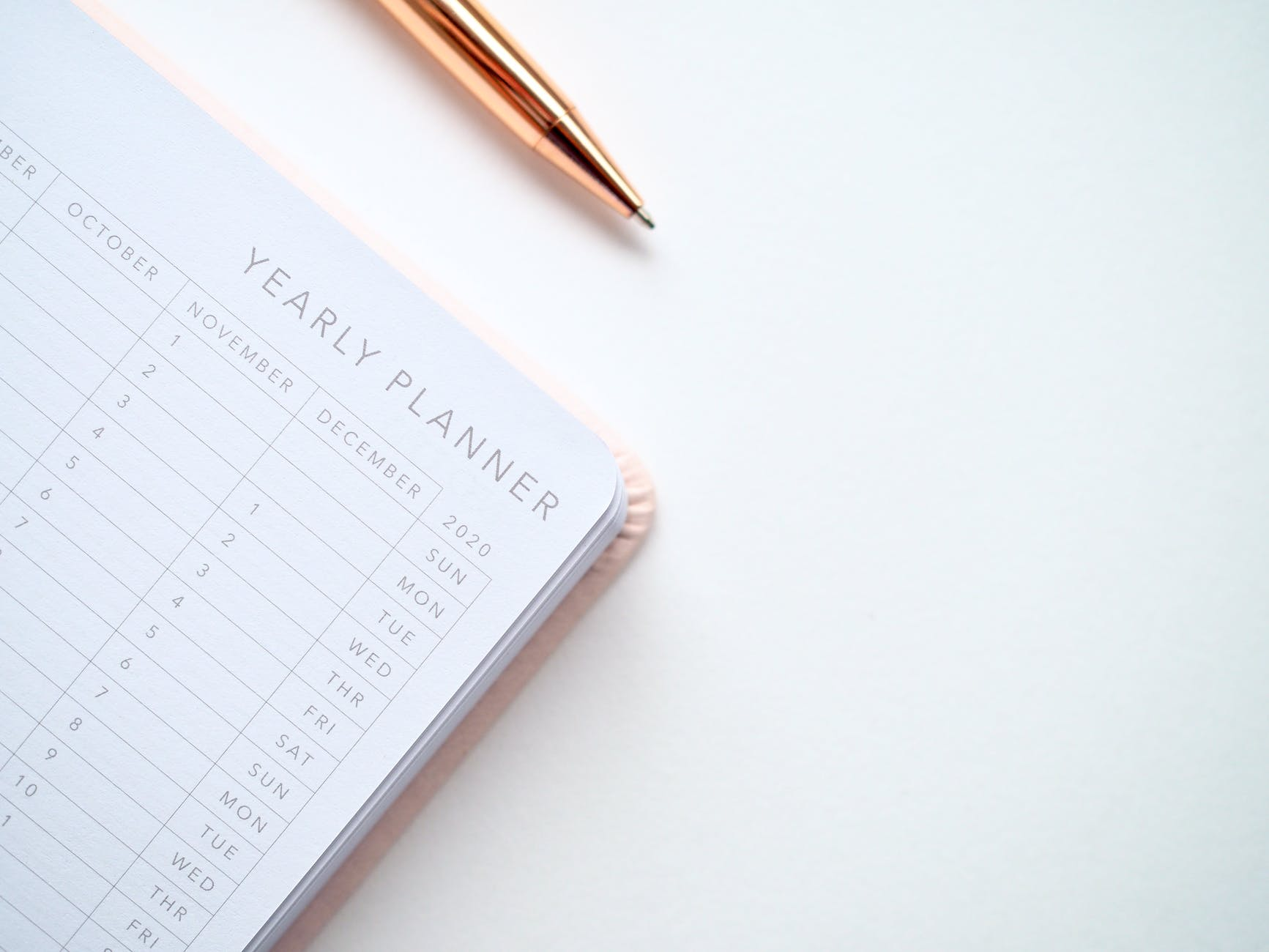 close up photo of yearly planner beside a pen